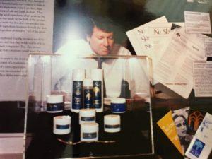 ニュースキン創業時の製品群と「伝説のスプーン」。背後の男性は若き日の創業者ブレイク ローニー